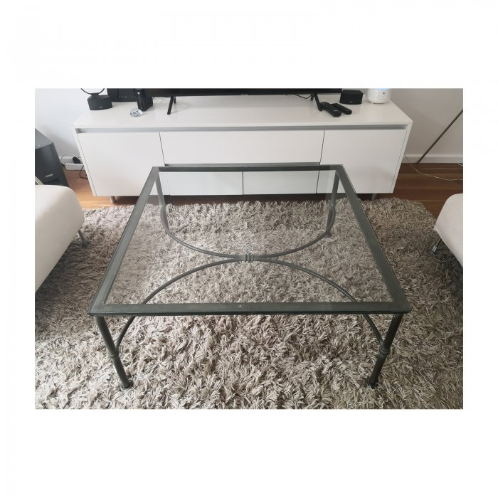 Wrought iron glass topped coffee table front on carpet